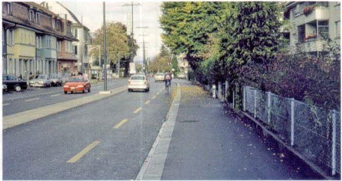 Районная улица на въезде с разделительной полосой, по которой возможен проезд, и выделенной велосипедной полосой