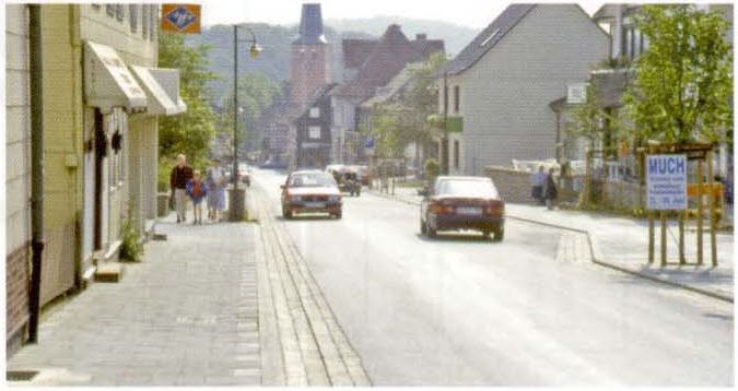Районная улица на въезде с широким мощенным лотком и изменяемым пространством по бокам проезжей части
