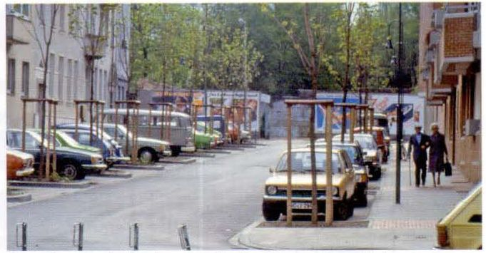 Улица в квартальной застройке с парковками, разделенными клумбами с деревьями