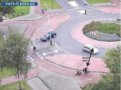 Явное обозначение приоритетов при помощи разметки типа «Уступи дорогу» (1.13). Расстояние в 5 метров необходимо для того, чтобы съезжающий с кольца автомобиль мог при необходимости остановиться, чтобы пропустить велосипедистов, не блокируя при этом движение по кольцу.